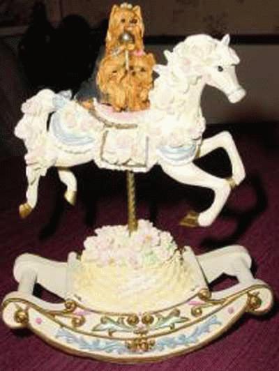 Drei Yorkies auf einem Karusell-Pferd